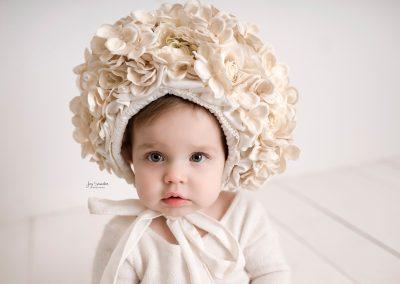 baby girl in white flower bonnet