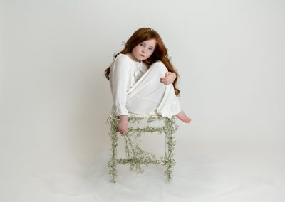 young red head girl sitting on flower stool